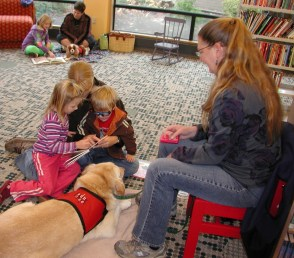 Reading with Rover volunteers and their dogs share the joy of reading with children at the Edmonds Library. (My Edmonds News file photo)