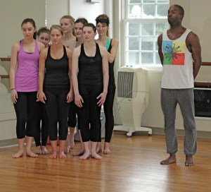 A group of dancers, with troupe member Nile Russell, watch as other dancers go through an exercise.