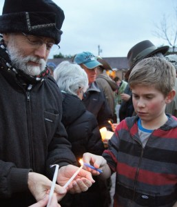 Attendees light their own candles.