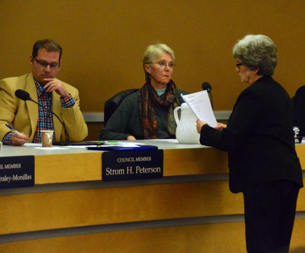 Linda Hynd of the City Clerk's office distributes ballots to councilmembers, including Strom Peterson, left, and Diane Buckshnis. (Photos by Larry Vogel)