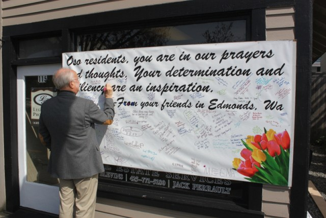 "Jack Perrault of Legendary Properties sent us this photo of Edmonds Mayor Dave Earling signing an oversized card for the Oso mudslide victims. Everyone is invited to drop by and sign the card at 115 5th Ave. S. in downtown Edmonds. ""We have had GREAT response and just put up another card to sign after the first  (4 foot x 8 foot) card filled in a day,"" Perrault said."