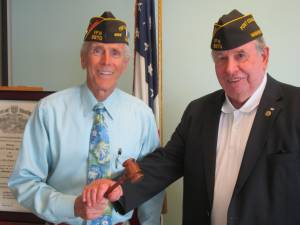 Outgoing Post Commander Fred Apgar passes the gavel to new Commander Jim Blossey.
