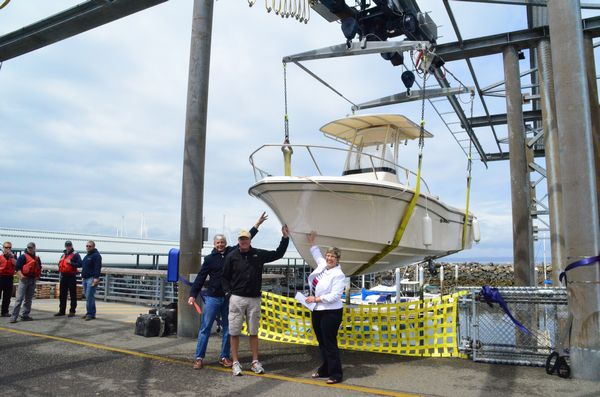 McChesney and Marla Kempt are joined by Greg Jacobsen (center) of Jacobsen Marine to officially welcome the first boat brought ashore on the newly dedicated launch.