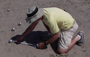Petanque is a game of inches (or more precisely, centimeters), with points scored according to the accuracy of the throw.  Here Tom Nunn of the Edmonds Petanque Club takes a measurement.