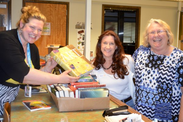 Scriber Lake High Librarian Leighann Law accepts books from Edmonds Rotary Noon Club organizer Elise Hegrat and Kim Gorney of Washington Kids in Transition.