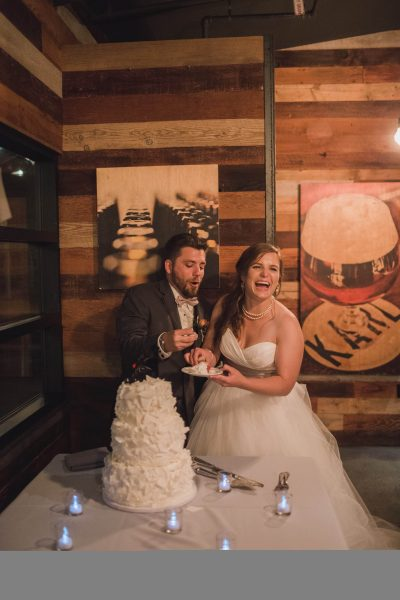 Natalie and Chris prepare for a time-honored wedding tradition: shoving cake into each other's faces.