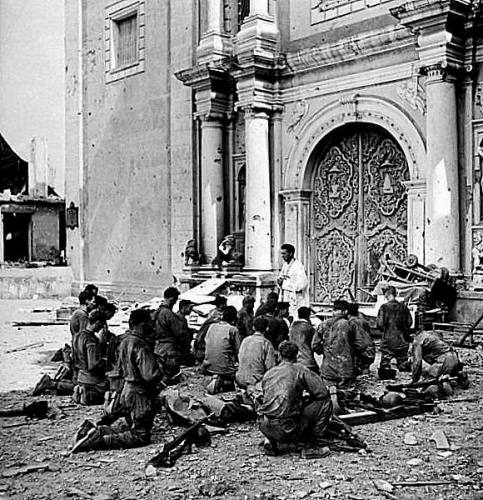 American soldiers praying in front of the ruins of San Agustan Church, Intramuros, Manila 1945