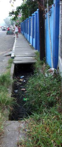 "Missing slabs show a typical ""sidewalk over sewer"" Philippine municipal sewer system in Tigbauan, Iloilo"