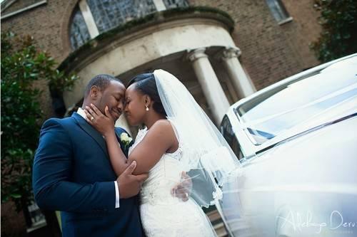 bride in wedding gown facing groom in dark wedding suit