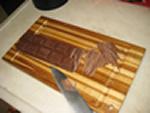 barra de chocolate cortada em lascas em uma tabua.