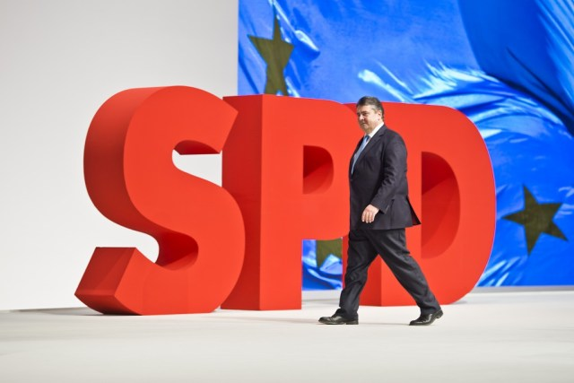 Sigmar Gabrial walking left past large SPD sign