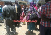 Disgruntled parents and their children mingle outside Mutoko magistrates' court after the postponement of the case