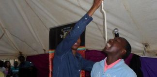Prophet Penuel Mnguni orders a member of his congregation to eat a live snake