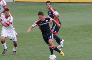 Revolution midfielder Ryan Guy pushes past D.C. United defender Perry Kitchen on Apr. 14. (Photo: Kari Heistad)