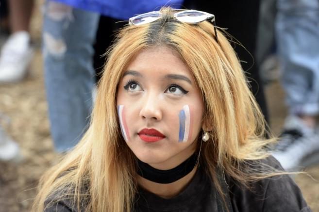 A France supporter watches the Euro 2016 tournament round of 16 football match between France and Republic of Ireland on June 26, 2016 at the Champ-de-Mars fanzone in Paris. / AFP PHOTO / ALAIN JOCARD