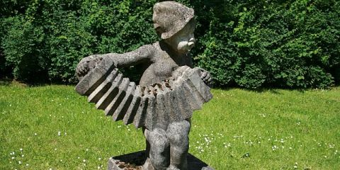 A statue of a child playing an accordion is shown.