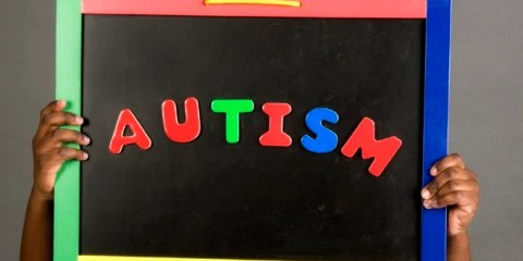 The image shows a child holding a sign with the word autism written on it.