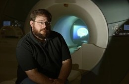 This image shows lead researcher, Stephen LaConte sitting in front of the fMRI machine.