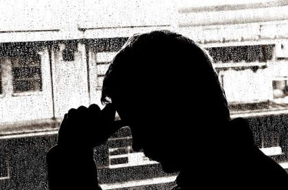 The image shows the outline of a man sitting by a window with rain falling.
