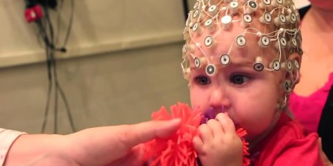 This image shows a baby chewing on a toy with an eeg helm on.