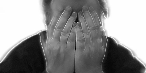 This image shows a man holding his head in pain.