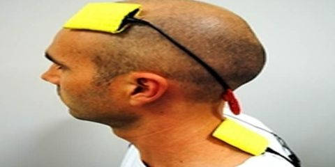 The image shows a person with the tDCS device on his head.