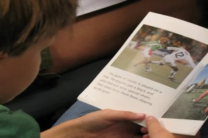 This image shows a a young boy reading a book about soccer