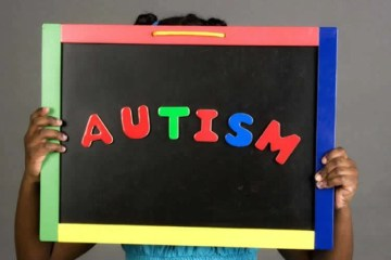 Image shows a girl holding up a sign with the work Autism written on it.