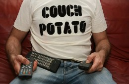 Image shows a person sitting on a couch with a t-shirt that reads couch potato.