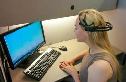 Image shows a woman in an EEG helm.