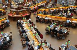 Image shows people studying in a library.
