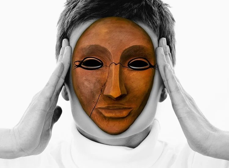 Image shows a woman in a wooden mask.