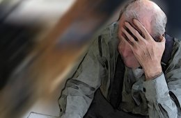 Image shows an old man holding his head.