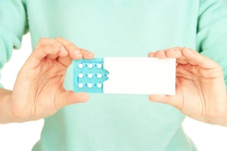 Image shows a woman holding pills.