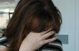 Image shows a depressed looking woman.
