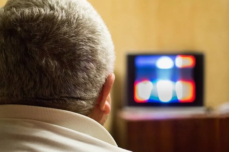 Image shows a man watching tv.