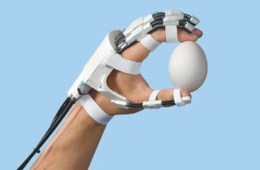 Image shows hand in an exoskeleton holding an egg.