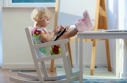 Image shows a little girl playing with a tablet.