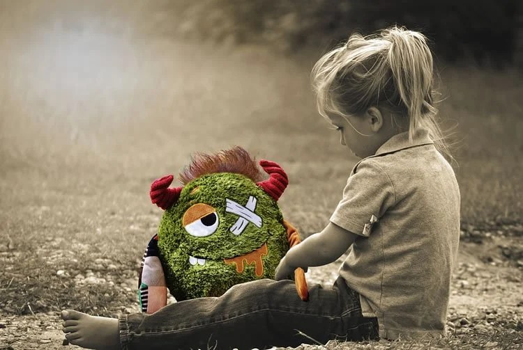 Image shows a little girl and a cuddly toy.