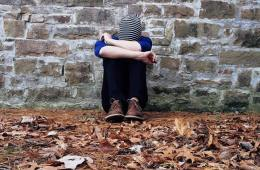 Image shows a person sitting next to a wall.