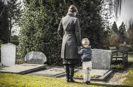 child and parent at grave yard