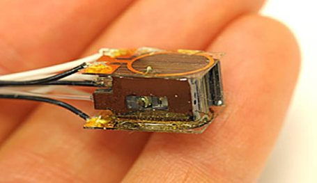 The atom-based magnetic sensor, about the size of a sugar cube is shown on human fingers.