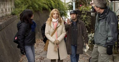 Director Takashi Shimizu (center right) confers with actress Sarah Michelle Gellar on location for THE GRUDGE.