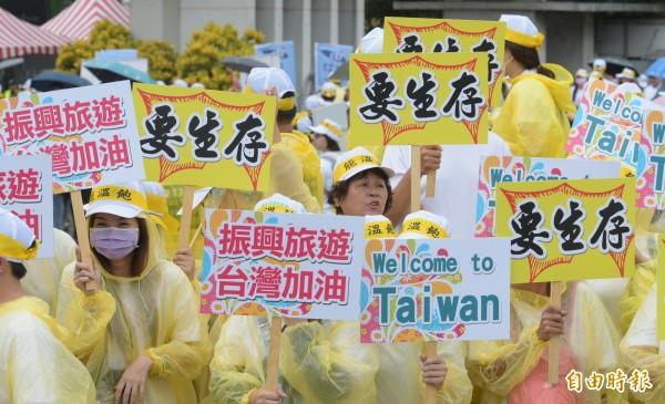 觀光旅行業者舉行觀光產業自救大遊行,抗議中國遊客縮減。 圖片來源:自由時報