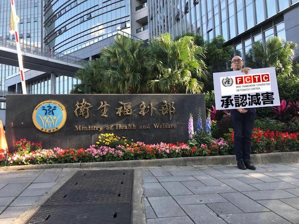 王郁揚曾到衛福部前舉牌抗議,表示WHO FCTC承認減害。 圖片來源:作者提供