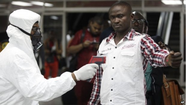 A Nigerian official uses a thermometer on a worker at Murtala Muhammed International Airport in Lagos, Nigeria on 6 August 2014