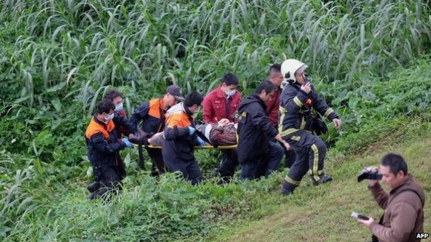 "Rescue personnel carry a passenger from a TransAsia ATR 72-600 turboprop plane that crash-landed into a river outside Taiwan""s capital Taipei on a stretcher in New Taipei City on February 4, 2015"