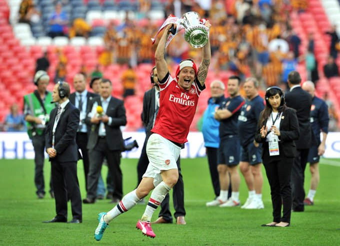 Arsenal's French striker Olivier Giroud runs with the trophy after winning the English FA Cup final match against Hull City at Wembly Stadium in London on May 17, 2014. Aaron Ramsey scored an extra-time winner as Arsenal ended their nine-year trophy drought by coming from two goals down to beat Hull City 3-2 in a gripping FA Cup final. AFP PHOTO/GLYN KIRK == NOT FOR MARKETING OR ADVERTISING USE / RESTRICTED TO EDITORIAL USE == (Photo credit should read GLYN KIRK/AFP/Getty Images)