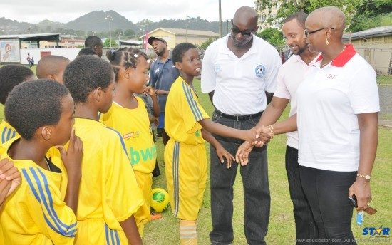 Castries Football Council President, Francis Daniel (extreme left); followed by ECFH Corporate Communications Manager, Omarie Frederick; and Permanent Secretary, Fortuna Belrose greet football players during the official opening of the Youth Football League.