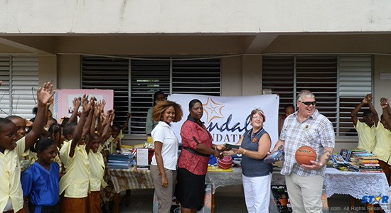 The children couldn't hide their joy as Brenda Joseph, Literary Coordinator at Roseau Combined accepted the donation from Sandals Foundation partners, Christine & Barry Scott.